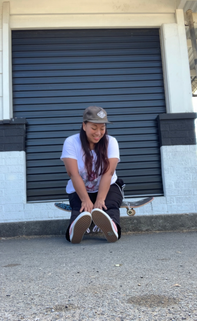 Indigo sitting on her skateboard in the street, looking down but smiling, background is black and white.